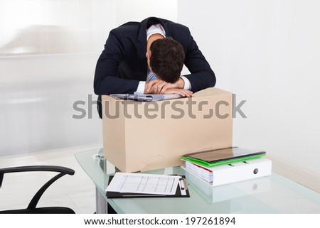 Tired businessman resting on cardboard box at desk in office - stock photo