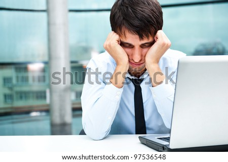 Tired businessman sleeping at his desk in the office with both arms on cheeks - stock photo
