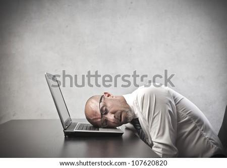 Tired businessman sleeping on his laptop's keyboard - stock photo