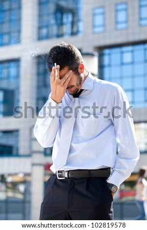 Tired businessman smoking while holding his head, having a cigarette break outside an office building