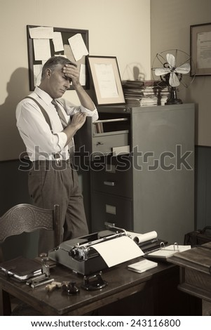 Tired businessman standing next to file cabinet touching his forehead.