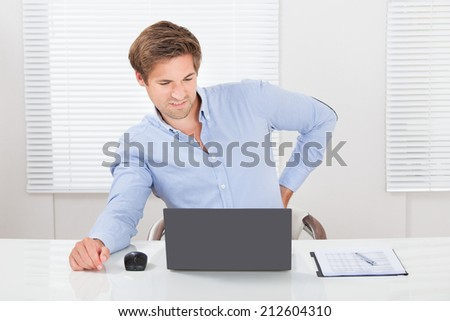 Tired businessman suffering from backache while working on laptop desk in office - stock photo
