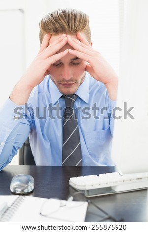 Tired businessman with his hands on face in his office
