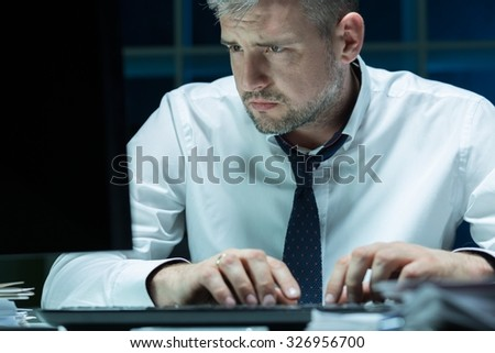 Tired businessman working at night in the office - stock photo