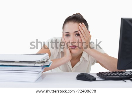 Tired businesswoman leaning on her desk against a white background