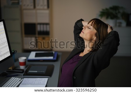 Tired Businesswoman Sitting at her Desk, Takes a Short Break to Relax While Working on her Computer. - stock photo