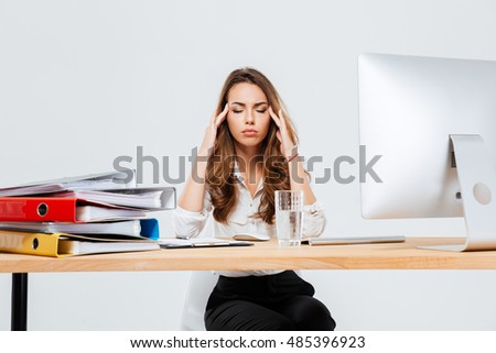 Tired businesswoman sitting at the table over white background