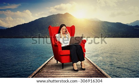 tired businesswoman sitting on the red chair on wood moorage over beautiful landscape - stock photo