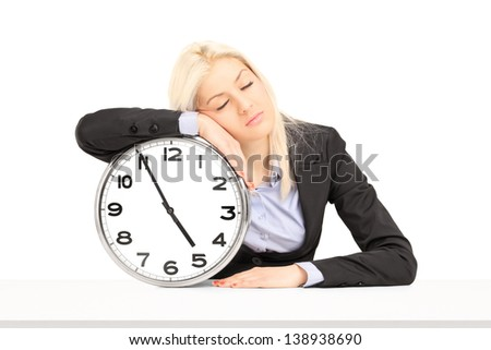 Tired businesswoman sleeping on a wall clock at workplace, isolated on white background - stock photo
