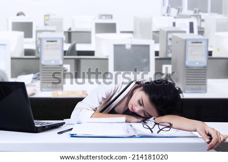 Tired businesswoman sleeping with laptop computer on the desk in office - stock photo