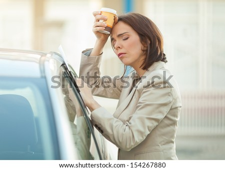 Tired businesswoman with a cup of coffee outdoors - stock photo