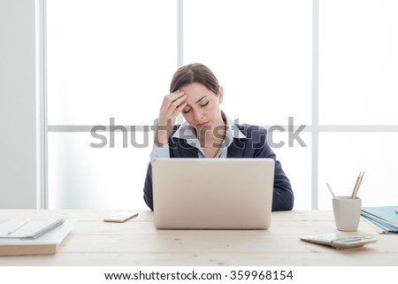 Tired businesswoman working with a laptop and touching her forehead, she is exhausted and having an headache, stressful job concept - stock photo