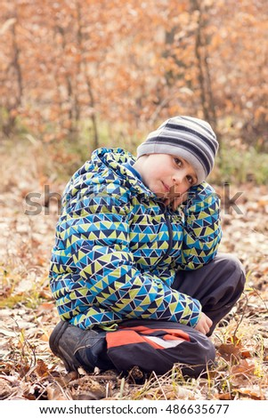 Tired child boy sitting on the ground in an autumn or fall forest