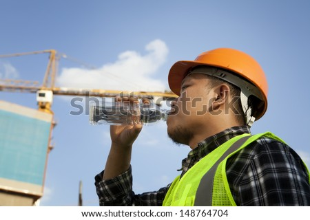 Tired construction worker drinking water with crane on the background - stock photo