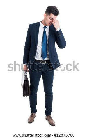 Tired corporate employee after work having a headache standing isolated on white background and holding briefcase - stock photo