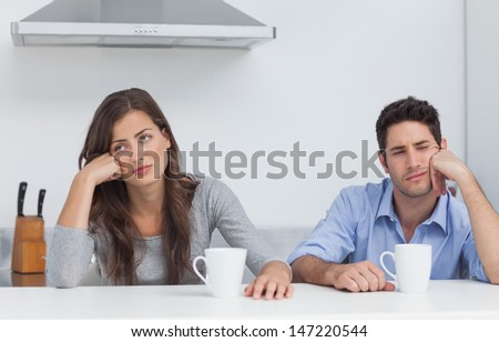 Tired couple sitting at the table with a cup of coffee in the kitchen - stock photo