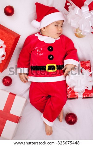Tired cute baby santa resting on presents