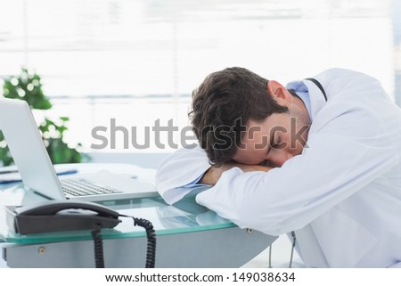 Tired doctor sleeping on his deck at medical office - stock photo