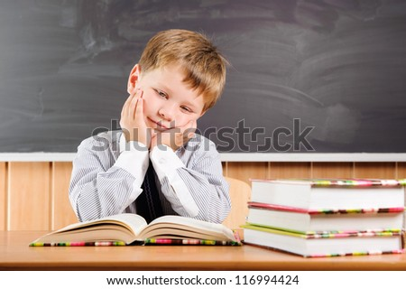 Tired elementary aged boy sitting at the desk with books