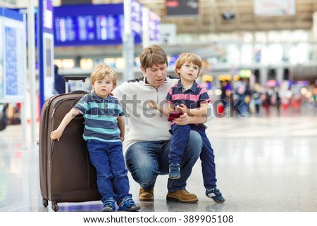 Tired father and two little sibling kids boys at the airport, traveling together. Upset family waiting. Canceled flight due to pilot strike. - stock photo