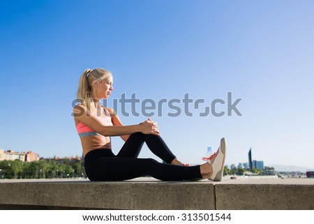 Tired female jogger taking break after fitness training while sitting on pier against blue sky background with copy space area for advertising, young sports woman enjoys resting after workout outdoors - stock photo