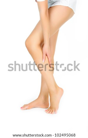 tired female legs being massaged with hand isolated on white background - stock photo