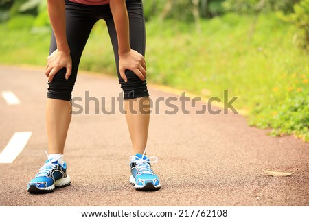 tired female runner taking a rest after running hard in countryside road. sweaty athlete after marathon training in country road.  - stock photo