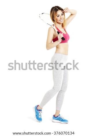 Tired female tennis player walking. Studio shot of attractive woman in sportswear. - stock photo