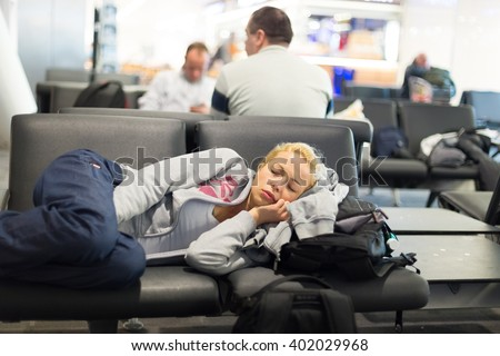 Tired female traveler sleeping on the airpot departure gates bench with all her luggage by her side.  Tireing travel concept. - stock photo