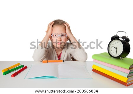 Tired first grader at a school Desk with a notebook, textbooks and alarm clock - stock photo