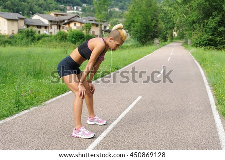 Tired fitness girl outdoors - stock photo