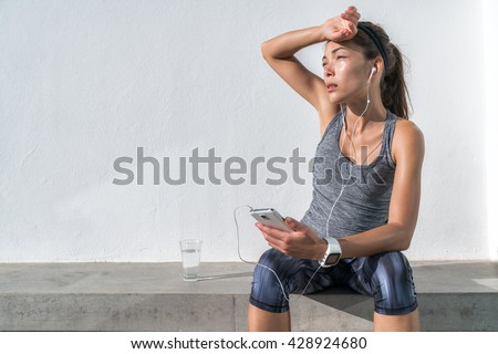 Tired fitness woman sweating taking a break listening to music on phone after difficult training. Exhausted Asian runner dehydrated feeling exhaustion and dehydration from working out at gym. - stock photo