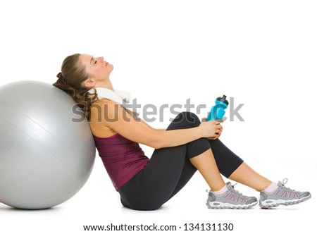 Tired fitness young woman relaxing after workout on fitness ball - stock photo