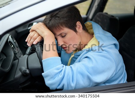 Tired Girl Driving a Car - stock photo