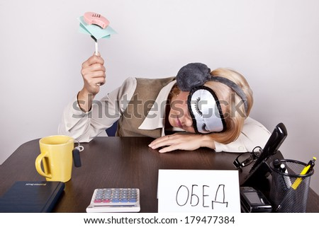 "Tired girl sleeping in the workplace with a bandage on the eyes, and the inscription ""lunch"" in Russian - stock photo"