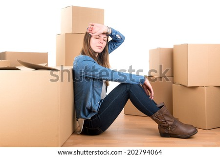 Tired girl with cardboard boxes unpacking in new home