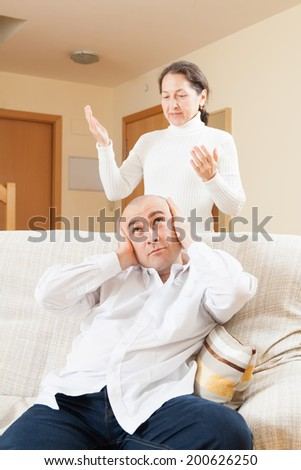 Tired guy listening to his angry woman at home - stock photo