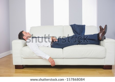 Tired handsome businessman lying on couch after work at home - stock photo