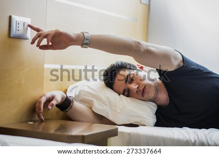 Tired Handsome Guy Switching Off the Light While Lying on his Side on the Bed with Eyes Closed. - stock photo