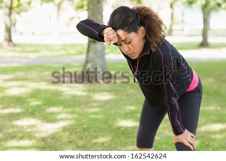 Tired healthy young woman taking a break while jogging in the park - stock photo