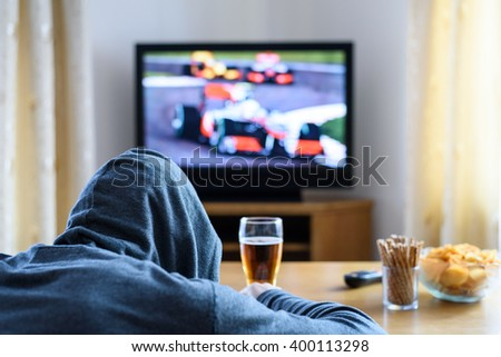 Tired hooded man falling asleep while watching TV (formula one race) in living room - stock photo