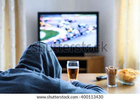 Tired hooded man falling asleep while watching TV (formula one race) in living room - stock photo - stock photo