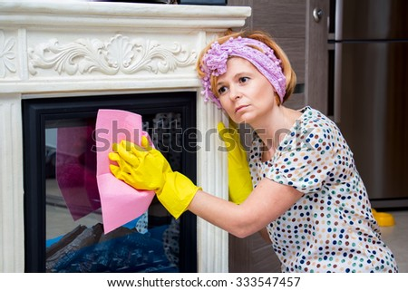 Tired housewife washes a fireplace in the living room