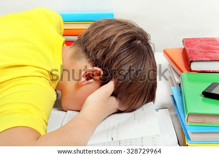Tired Kid doing Homework on the Bed in the Room - stock photo