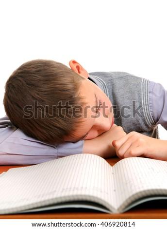 Tired Kid Sleep on the School Desk on the White Background - stock photo
