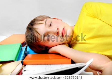 Tired Kid sleep with the Books on the Bed - stock photo