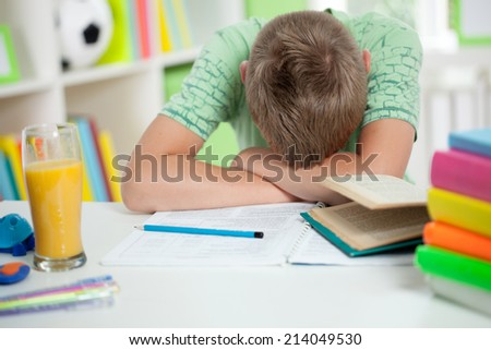 Tired Kid Sleeping on the Desk at home - stock photo
