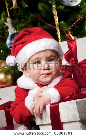 Tired little boy with a gift boxes. - stock photo