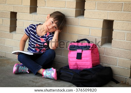 Tired little girl after a long day at school - stock photo