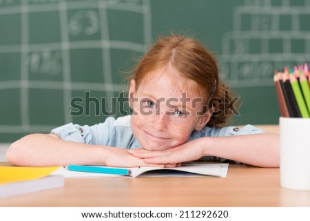 Tired little girl in class in school giving a rueful smile as she rests her head on her hands on the desk - stock photo